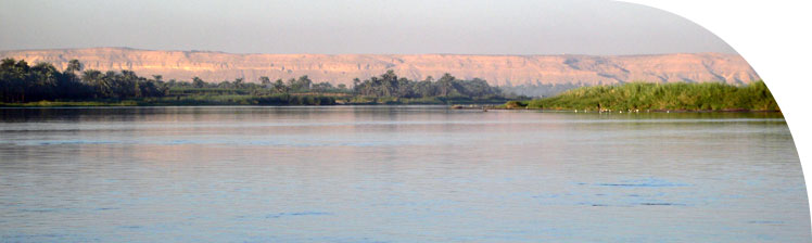 Downstream view of the eastern cliffs behind Amarna, as the river swings past them to the left.