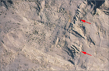 Aerial photograph of small surface quarries on the desert above Queen Tiy's quarry. The red arrows mark the positions of two sets of shallow quarries
