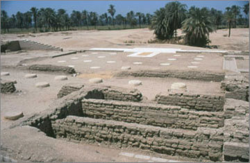 View of the central columned hall. The positions of the missing column bases are represented by circular pads made from a mixture of white stone chippings and white cement. The stonework in the background marks the outline of a staircase or ramp which led up to a platform. The orignal stone blocks had been removed at the end of the Amarna Period, but their impressions remained in layer of gypsum concrete