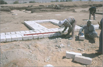 Masons at work laying the new stone blocks which mark the outline of the ancient stonework. The ancient layer of gypsum concrete which provides the evidence for the original presence of this stonework is buried beneath a thick layer of sand. The stone blocks are cut approximately to the ancient dimensions
