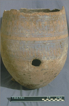 Blue-painted storage jar that was converted into a small kiln or oven. The hole near the base allowed the entry of air and of fuel