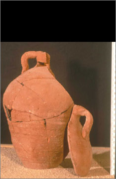 One of a group of nine similar pottery vessels from the monastery at Kom el-Nana (catalogue no. 424) in which a panel from the shoulder, with its own handle, has been separately made. All examples have a hole in the base and some have holes pierced on the shoulder. The purpose of these vessels is not known.